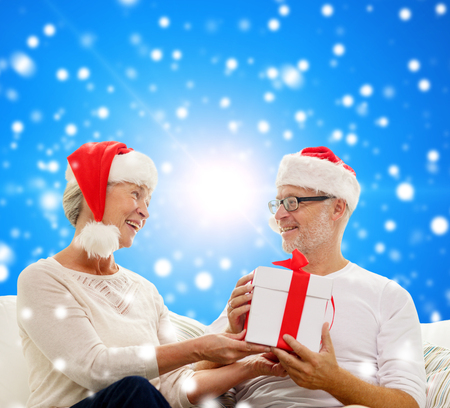 family, holidays, christmas, age and people concept - happy senior couple with gift box over blue snowy background photo