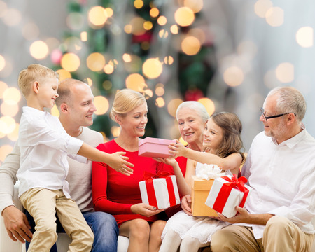 smiling: family, holidays, generation, christmas and people concept - smiling family with gift boxes sitting on couch over tree lights background
