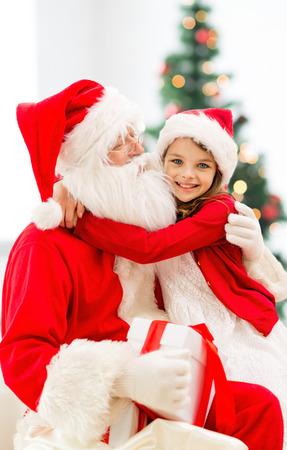 サンタ クロースとクリスマス ツリーのライトの背景に抱いて少女の笑みを浮かべて - 休日、お祝い、子供の頃、人々 の概念