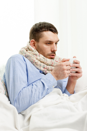 flue season: healthcare, people and medicine concept - ill man in scarf holding cup with hot drink at home Stock Photo