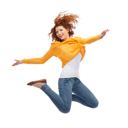 air jump: happiness, freedom, movement and people concept - smiling young woman jumping in air