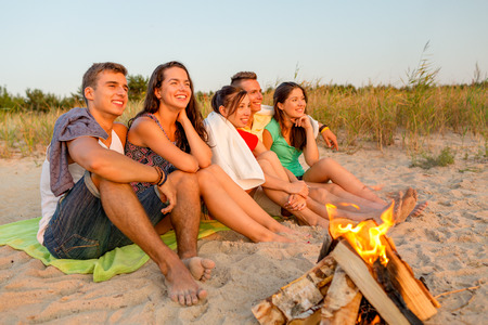 friendship, happiness, summer vacation, holidays and people concept - group of smiling friends sitting near fire on beach