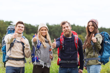 travel, tourism, hike, gesture and people concept - group of smiling friends with backpacks standing and showing thumbs up outdoors photo