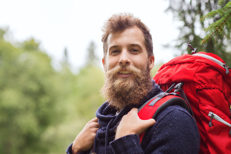 people travelling: adventure, travel, tourism, hike and people concept - smiling man with beard and red backpack hiking