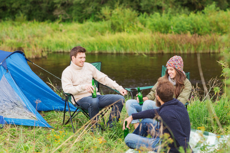 adventure, travel, tourism, friendship and people concept - group of smiling tourists drinking beer in camping photo