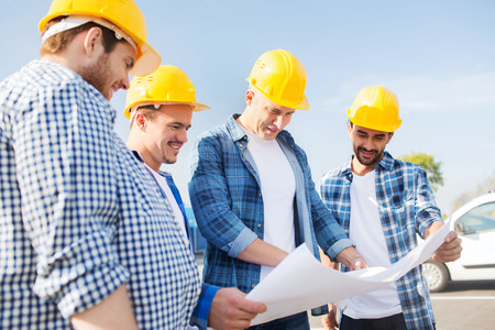 urban planning: business, building, teamwork and people concept - group of smiling builders in hardhats with blueprint outdoors Stock Photo