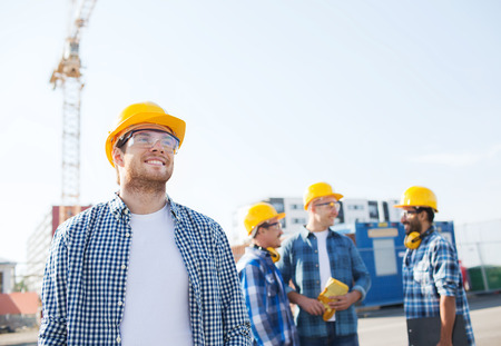 constructors: business, building, teamwork and people concept - group of smiling builders in hardhats with clipboard outdoors Stock Photo