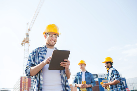 business, building, teamwork, technology and people concept - group of smiling builders in hardhats with tablet pc computer outdoors Stock Photo
