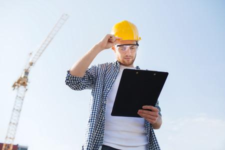 alba�il: negocio, construcci�n, tr�mites y concepto de la gente - constructor en el casco con el portapapeles al aire libre