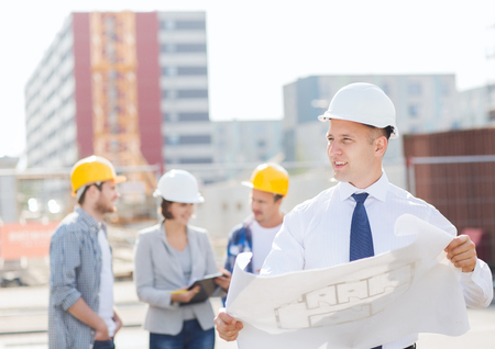urban planning: business, building, teamwork and people concept - group of smiling builders in hardhats with clipboard and blueprint outdoors