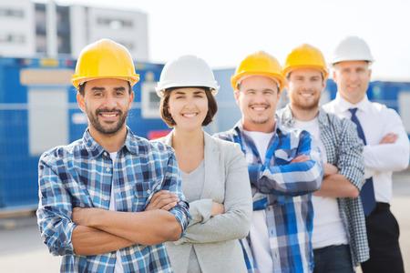 bedrijfsleven, de bouw, teamwork en mensen concept - groep van lachende bouwers in bouwvakkers buiten