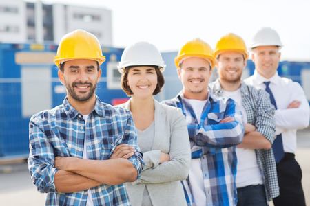 business, building, teamwork and people concept - group of smiling builders in hardhats outdoors photo