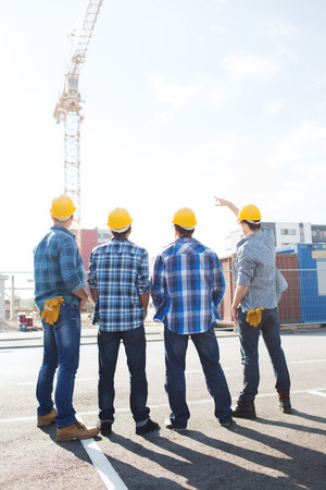 work area: business, building, teamwork and people concept - group of builders in hardhats outdoors from back Stock Photo