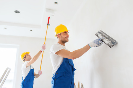 wall covering: business, building, teamwork and people concept - group of smiling builders in hardhats with plastering tools indoors Stock Photo