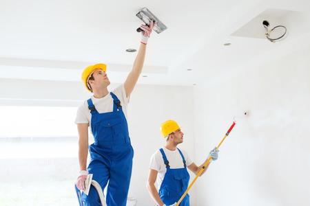 hombre pintando: negocio, construcci�n, trabajo en equipo y concepto de la gente - grupo de constructores en cascos con enlucido herramientas interiores Foto de archivo