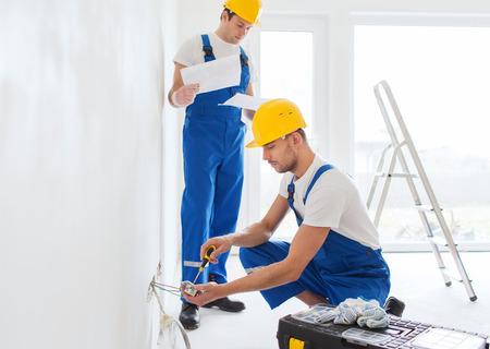 mantenimiento: la construcción, renovación, la tecnología, la electricidad y el concepto de la gente - dos constructores con ordenador Tablet PC que trabajan con el interior de la electricidad