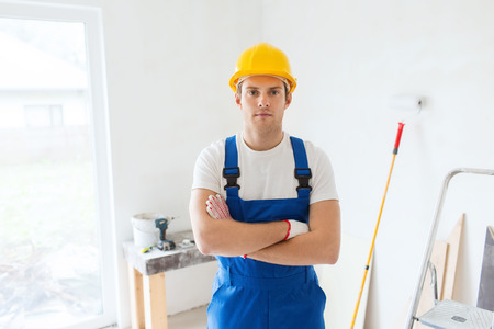 painter and decorator: building, repair and people concept - builder in hardhat and overall with working tools indoors