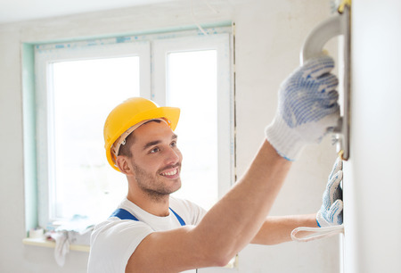 priming: building, profession and people concept - smiling builder in hardhat sanding wall indoors