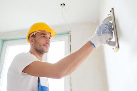 建物は、職業や人々 コンセプト - ヘルメット紙やすりで磨く壁を屋内でビルダー 写真素材