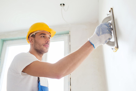 sanding: building, profession and people concept - builder in hardhat sanding wall indoors Stock Photo