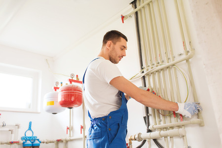 building, profession and people concept - builder or plumber working with water pipes in boiler room Stockfoto