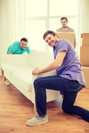 large group of items: moving, real estate and friendship concept - smiling male friends with sofa and boxes at new home