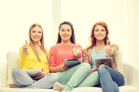 friendship, technology and internet concept - three smiling teenage girls with tablet pc computers at home showing thumbs up photo