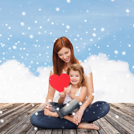 day care: childhood, parenting, love and people concept - happy mother with little girl and red heart over wooden floor and blue sky background