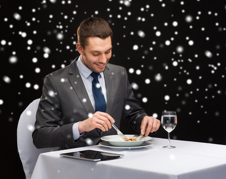 main course: food, people, technology and holidays concept - smiling man with tablet pc eating main course at restaurant over black snowy background Stock Photo