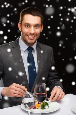 reviewer: food, people, technology and holidays concept - smiling man with tablet pc eating main course at restaurant over black snowy background Stock Photo