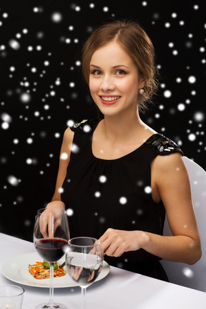 reviewer: food, people, technology and holidays concept - smiling woman with tablet pc eating main course at restaurant over black snowy background