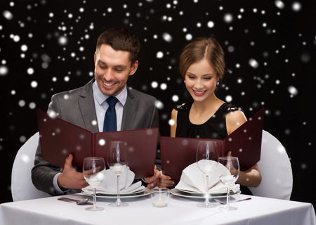 food, christmas, holidays and people concept - smiling couple with menus at restaurant over black snowy background photo