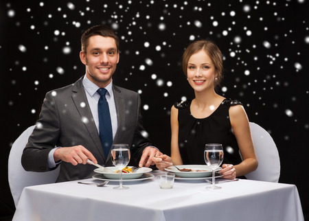 food, christmas, holidays and people concept - smiling couple eating main course at restaurant over black snowy background photo