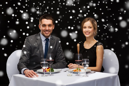 main course: food, christmas, holidays and people concept - smiling couple eating main course at restaurant over black snowy background