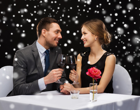 clinking: celebration, christmas, holidays and people concept - smiling couple clinking glasses of red wine at restaurant over black snowy background