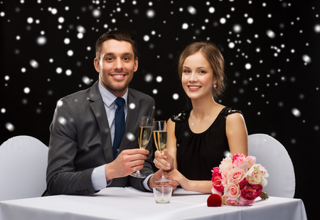 celebration, christmas, holidays and people concept - smiling couple clinking glasses of sparkling wine at restaurant over black snowy background photo