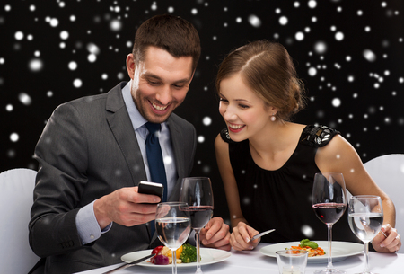 technology, food, christmas, holidays and people concept - smiling couple with smartphone eating at restaurant over black snowy background photo