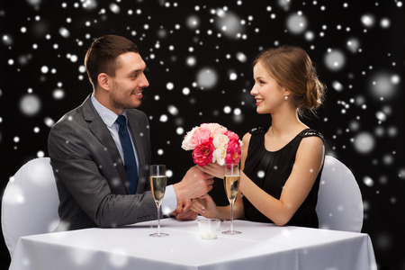 celebration, christmas, holidays and people concept - smiling couple with champagne and flowers at restaurant over black snowy background photo
