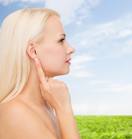visage femme profil: concept de santé et de beauté - gros plan de visage propre de la belle jeune femme pointant le doigt à l'oreille