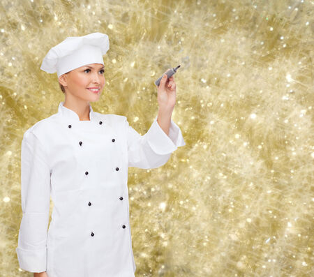 cooking, holidays, advertisement and people concept - smiling female chef, cook or baker with marker writing something on virtual screen over yellow lights background photo
