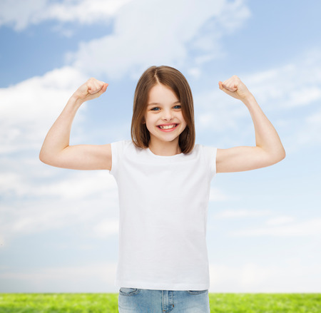 advertising, childhood, summer, gesture and people concept - smiling little girl in white t-shirt with raised arms over natural background photo