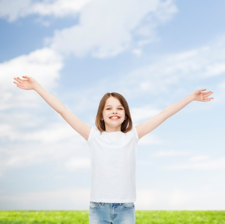 stretched: advertising, childhood, gesture and people concept - smiling little girl in white t-shirt with stretched out arms over natural background