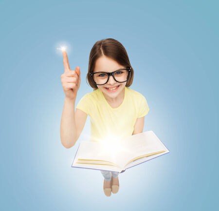 little finger: education and school concept - smiling little student girl in eyeglasses with book and finger up