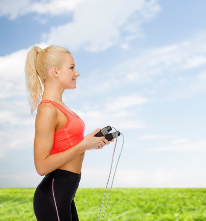 woman rope: sport, exercise and healthcare concept - smiling sporty woman with skipping rope Stock Photo