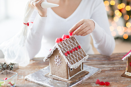 cooking, people, christmas and decoration concept - close up of happy woman making gingerbread houses at home photo