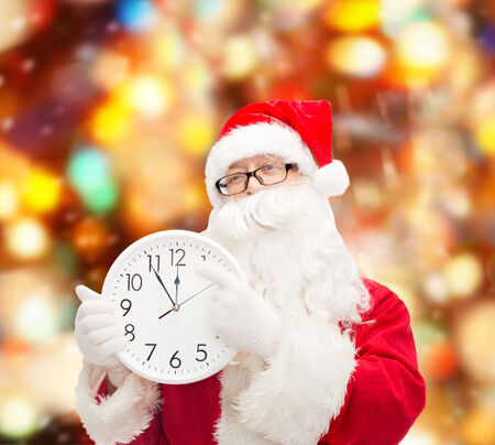 twelve month old: christmas, holidays and people concept - man in costume of santa claus with clock showing twelve over red lights background