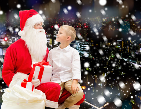 nicolas: holidays, christmas, childhood and people concept - smiling little boy with santa claus and gifts over snowy city background Stock Photo