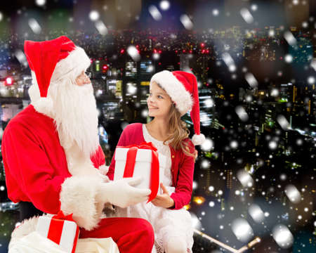 holidays, christmas, childhood and people concept - smiling little girl with santa claus and gifts over snowy city background photo