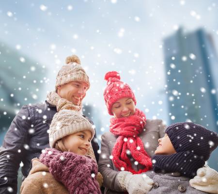 Famiglia, l'infanzia, la stagione e la gente concept - famiglia felice in abiti invernali su sfondo di città nevosa Archivio Fotografico - 34051452