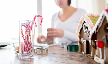 sugarcoated: cooking, people, christmas and decoration concept - happy woman making gingerbread houses at home
